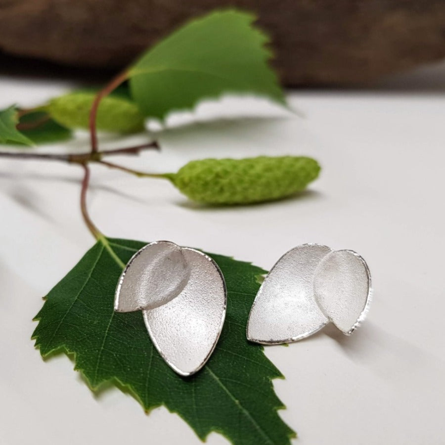 View and buy ethical handmade jewellery online at The Biscuit Factory. 'Fritillaria Petal Earrings' silver floral studs by Donna Barry. Image shows a pair of stud earrings each made up of two pointed ovals one smaller than the other sat on a leaf against a white background.