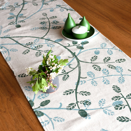 printed textile table runner by Astrid Weigel. Image shows a linen coloured table runner printed with green and blue leaves, sat on a polished wood table and accompanied by a grey vase with flowers and a trio of unusual shaped green ceramics.