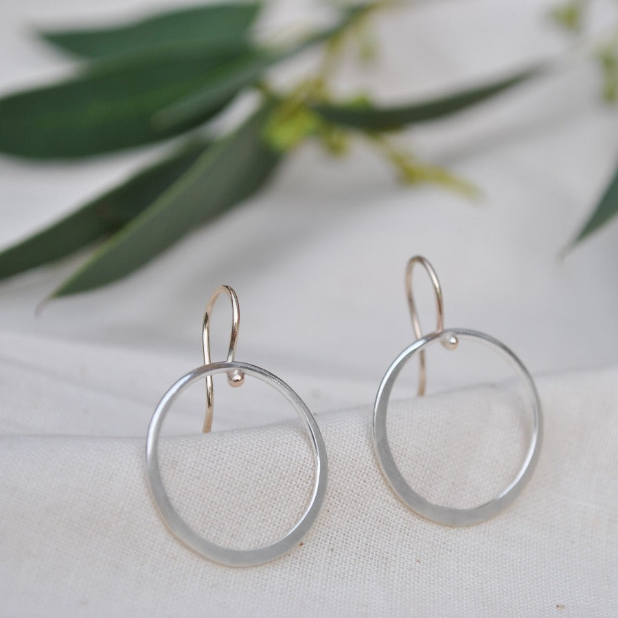 Buy 'Drop Hoop Earrings' handcrafted jewellery by Sarah Ruth Stanford. Image shows a pair of earrings sat upright on beige linen with green leaves blurred in the background. The earrings have gold ear wires and a large silver hoop forming the drop.