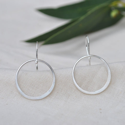 Buy 'Silver Hoop Drop Earrings' handcrafted jewellery by Sarah Ruth Stanford. Image shows a pair of silver drop earrings with s-shaped ear hooks and a hollow ring of silver forming the drop. They are sat upright on beige linen and green leaves are in the background