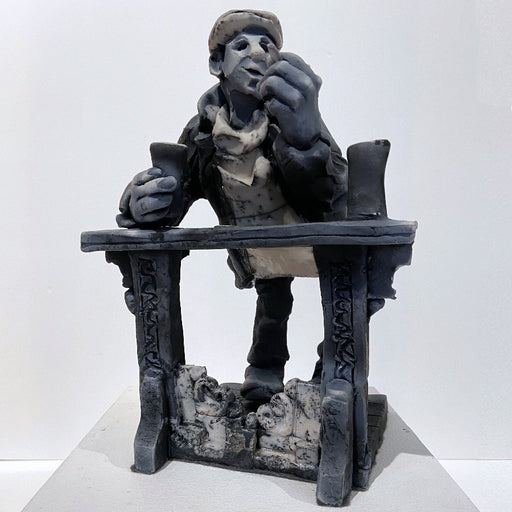 Buy 'Propping up the Bar', a ceramic sculpture by Yorkshire artist Alistair Brookes. Image shows a grey stylised sculpture of a man wearing bulky clothes and a peaked hat leaning against a table. The sculpture is sat on a white plinth against a white wall.