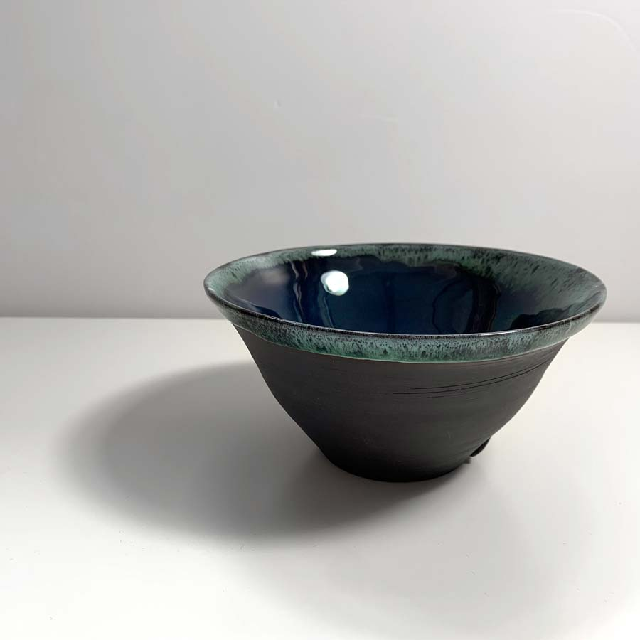 Buy 'Cobalt Fluted Bowl', a ceramic bowl by Kirsty Adams. Image shows a black porcelain bowl with a green/blue glaze inside and spilling out around the rim. The background is white and pale grey