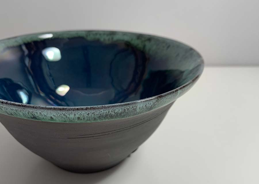 Buy 'Cobalt Fluted Bowl', a small ceramic bowl by Kirsty Adams. Image shows a close up of a black porcelain bowl with a green/blue glaze. The close up shot details the wave like effect of the glaze speckled with lighter and darker tones. The background is white.