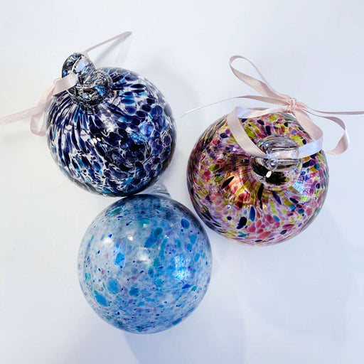 Buy 'Bauble' a blown glass Christmas decoration by Jane Charles. Image shows 3 glass spheres, 2 sat up right showing a glass hook with a pink ribbon fastened in each. The glass is decorated with marbled colours, predominantly purple. The background is white.