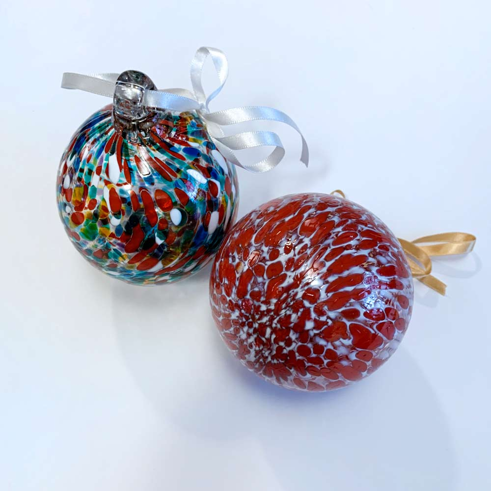 Buy 'Bauble' a blown glass Christmas decoration by Jane Charles. Image shows 2 glass spheres, 1 sits up right showing a glass hook with a white ribbon fastened to it. The glass is decorated with marbled colours, predominantly red. The background is white.