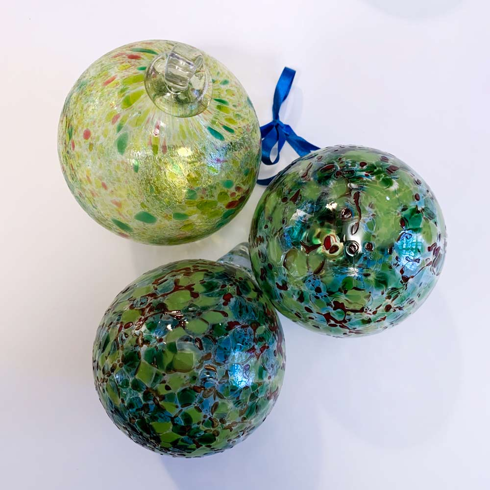 Buy 'Bauble' a blown glass Christmas decoration by Jane Charles. Image shows 3 glass spheres, 1 sits up right showing a glass hook. The glass is decorated with marbled colours, predominantly green. The background is white.