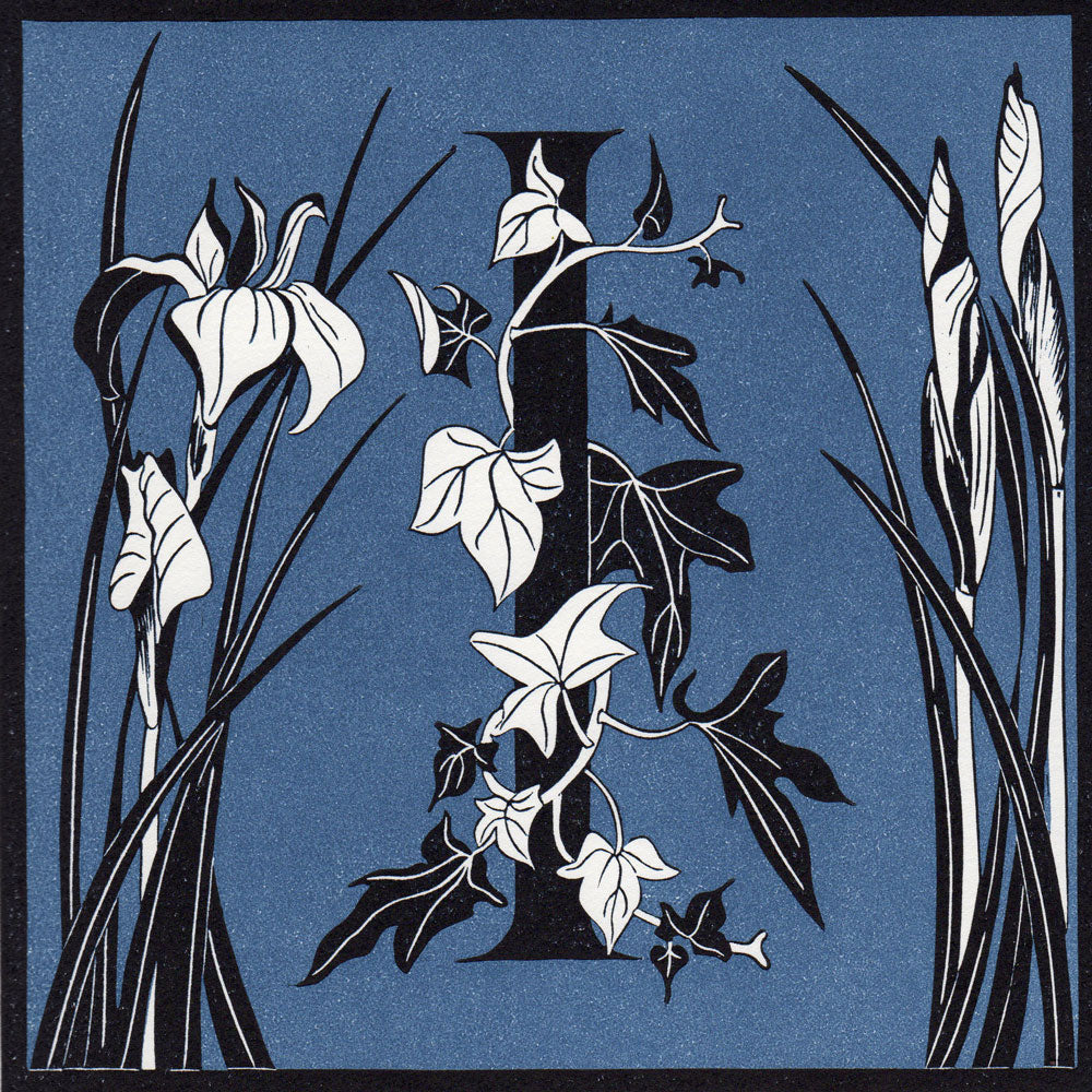 View and buy typography prints by Julie North at The Biscuit Factory. Image shows a blue square with a black border featuring the letter I at the center wrapped in ivy and flanked by irises