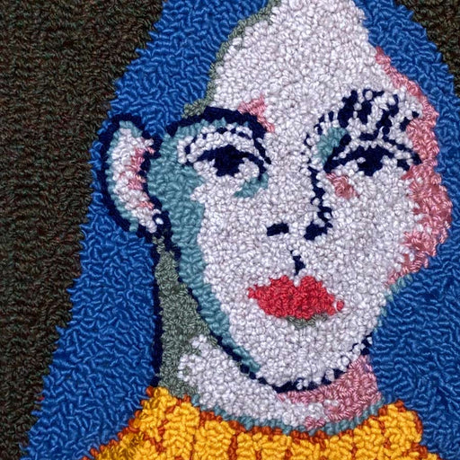 'It's just for fun', a tapestry wall hanging by textile artist Selby Hurst Inglefield. Image shows a tapestry portrait of a person with pale skin and royal blue hair wearing a yellow top on a dark grey background.