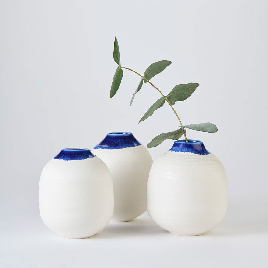 Buy 'Small White and Cobalt Moon Jar', a rounded ceramic vessel by Kirsty Adams. Image shows three small rounded white pots with a short, slightly fluted neck coloured in a vivid blue glaze. The pots form a triangle and are shot front on. In the leftmost pot a stem of green leaves sprouts from inside. The vases sit on a pale grey background.