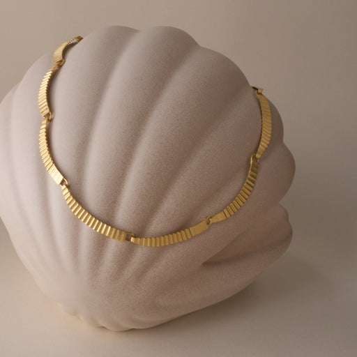 View and buy handmade jewellery from recycled metals by Clara Breen at The Biscuit Factory. Image shows a gold necklace made up of curved and crimped segments resting upon a beige coloured shell-shaped figure.