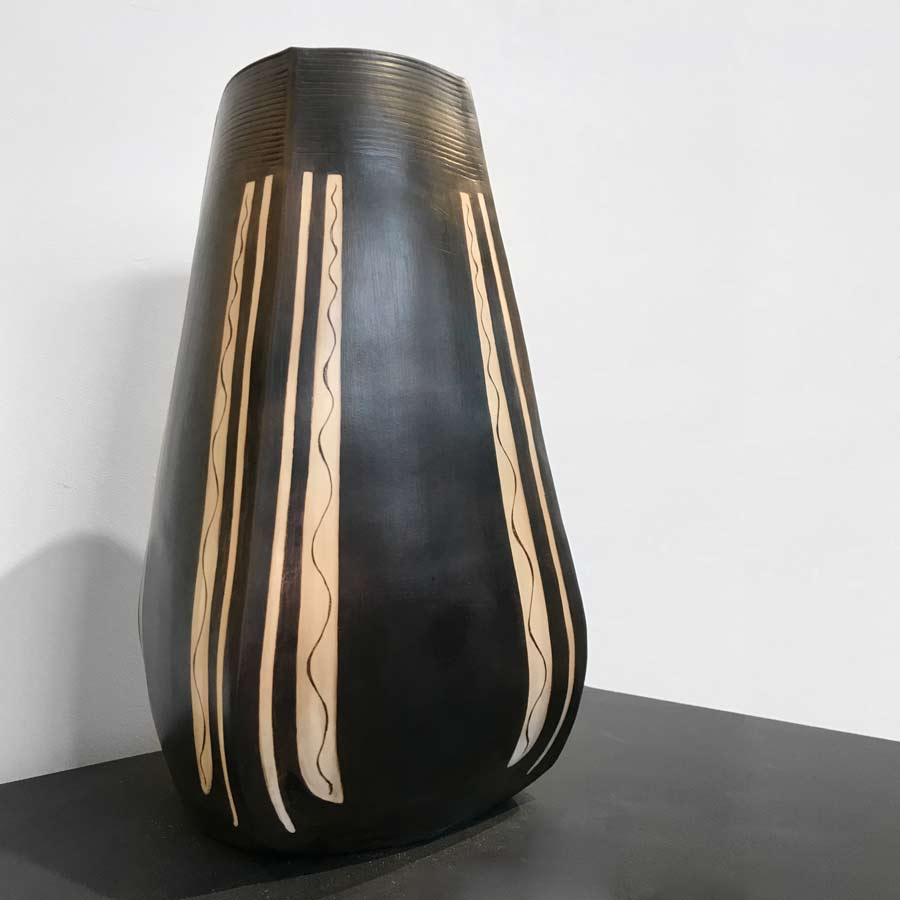 'LH1', a large ceramic pot by Laura Hancock. Image shows a 4 sided dark brown pot decorated with white lines at the edges of each side sat on a black plinth against a white wall