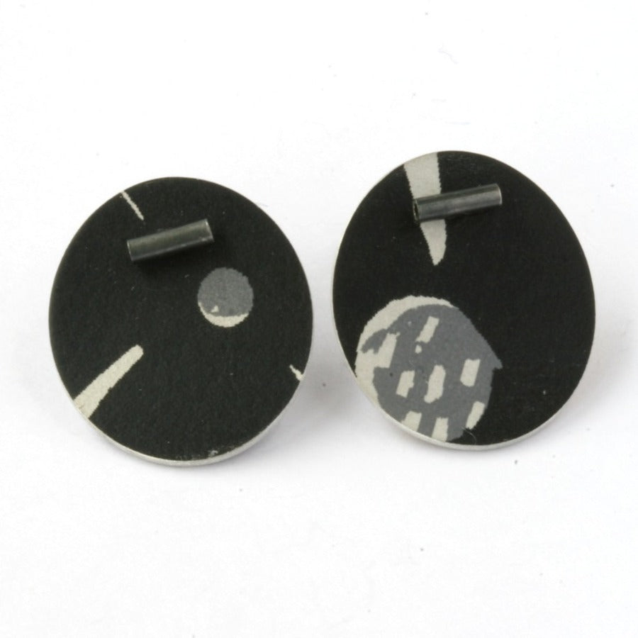Buy 'Large Pattern Studs' handcrafted earrings by Lindsey Mann. Image shows a pair of circular disc earrings in black sat upright on a white background. They are decorated with asymmetrical white and grey mark-making patterns - circles, dashes, lines. A tube of dark metal sits under the top edge of each.