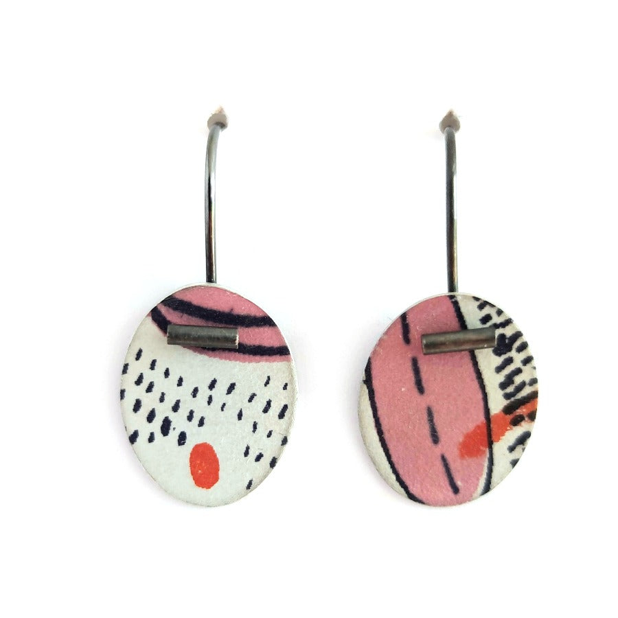 Buy 'Small Pattern Drops' handcrafted earrings by Lindsey Mann. Image shows two white discs hanging from s-shaped ear wires sat upright on a white background. The discs are decorated with pink shapes, navy mark-making and red smudges. A dark metal tube sits at the tip of the disc of each earring.