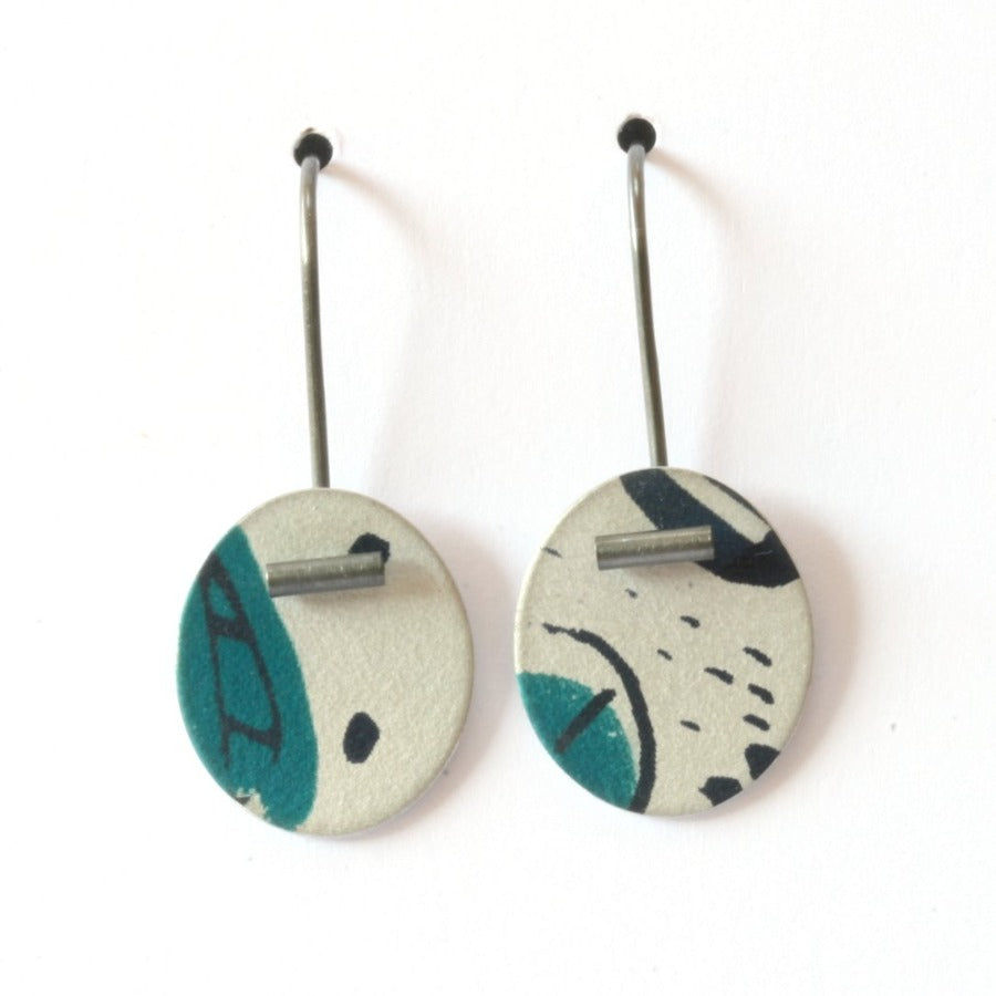 Buy 'Small Pattern Drops' handcrafted earrings by Lindsey Mann. Image shows two white discs hanging from s-shaped ear wires sat upright on a white background. The discs are decorated with turquoise shapes, navy mark-making and smudges. A silver metal tube sits at the tip of the disc of each earring.