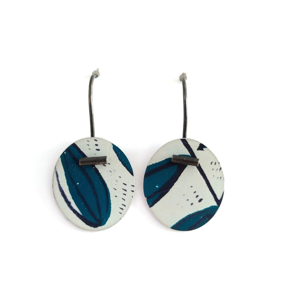 Buy 'Large Pattern Drops' handcrafted earrings by Lindsey Mann. Image shows two white discs hanging from s-shaped ear wires sat upright on a white background. The discs are decorated with turquoise shapes, black mark-making and smudges. A dark metal tube sits at the tip of the disc of each earring.