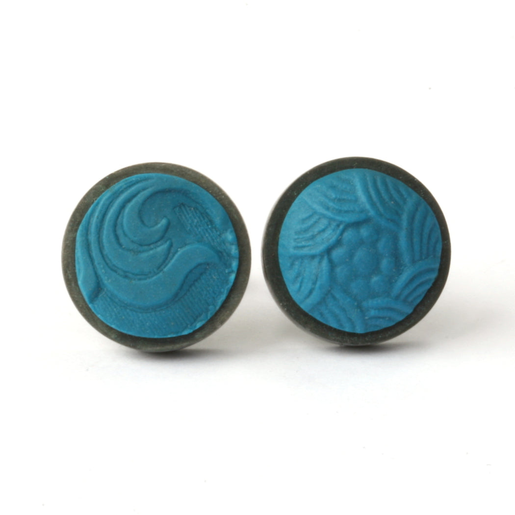 Buy 'Round Button Studs' handcrafted earrings by Lindsey Mann. Image shows a pair of turquoise polymer circular earrings set in oxidised silver. The Polymer is stamped with different patterns - one circular bumps and the other scroll-like. They sit upright on a white background.