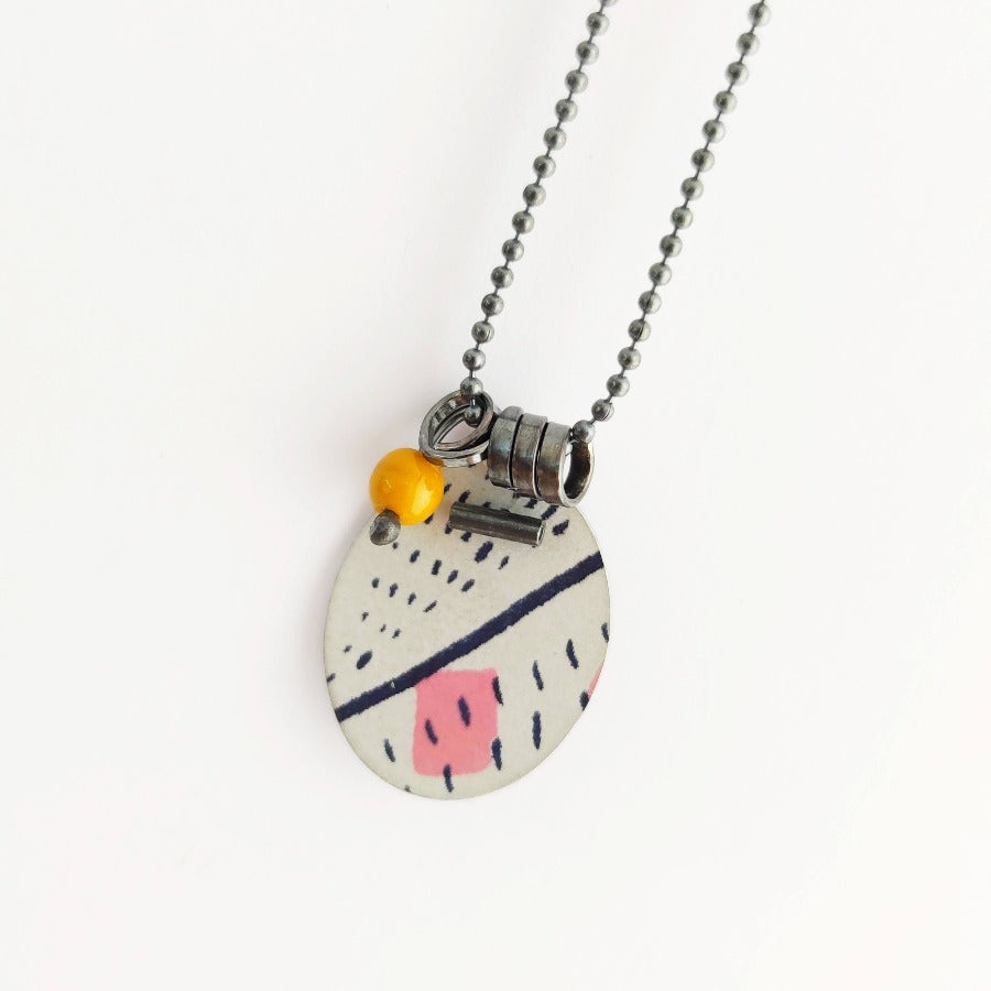Buy 'Pattern Pendant' handcrafted necklace by Lindsey Mann. Image shows a white oval disc pendant lying on a white background attached to an oxidised ball chain with 3 rings. The disc is decorated by a pink square, navy dashes and lines. Also hanging from the chain is a yellow glass bead.