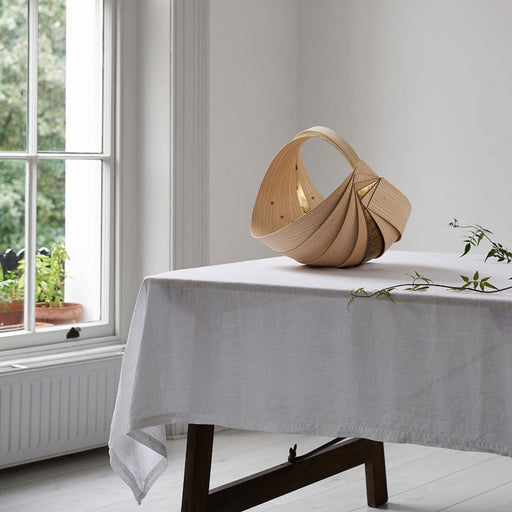 Buy handmade sculpture/homeware by Jane Crisp at The Biscuit Factory. Image shows a large spiral wooden basket made of ash and brass panels sat on top of a trundle table with a white table cloth in front of a large sash window.