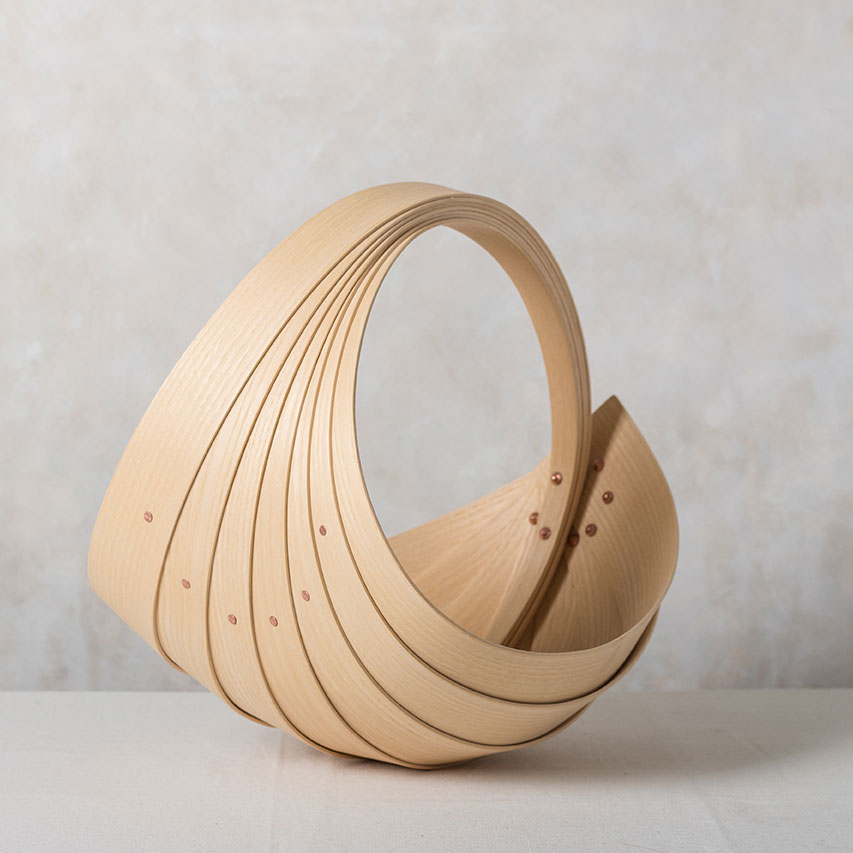 Buy handmade original homeware by Jane Crisp at The Biscuit Factory. Image shows a sculptural wooden spiral basket with copper pins sat in a light grey marble background
