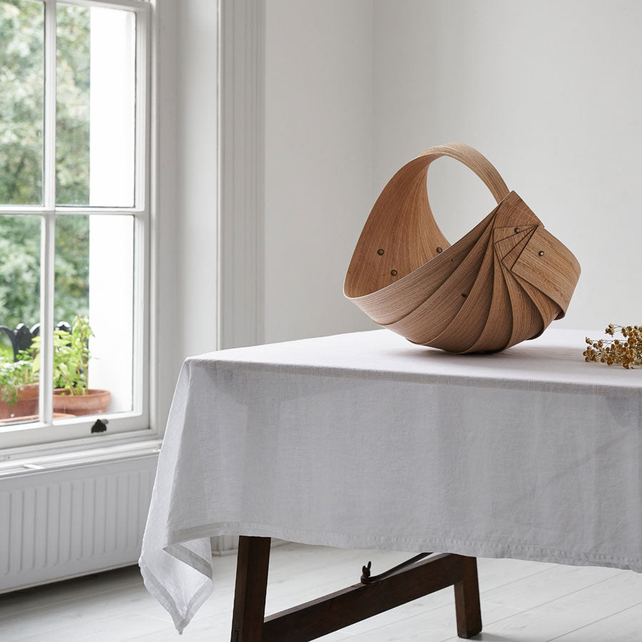 Buy handmade original homeware by Jane Crisp at The Biscuit Factory. Image shows a sculptural wooden spiral basket made with oak panels and leather fastening details. Basket sits on a trundle table with a white table cloth in front of a large sash window