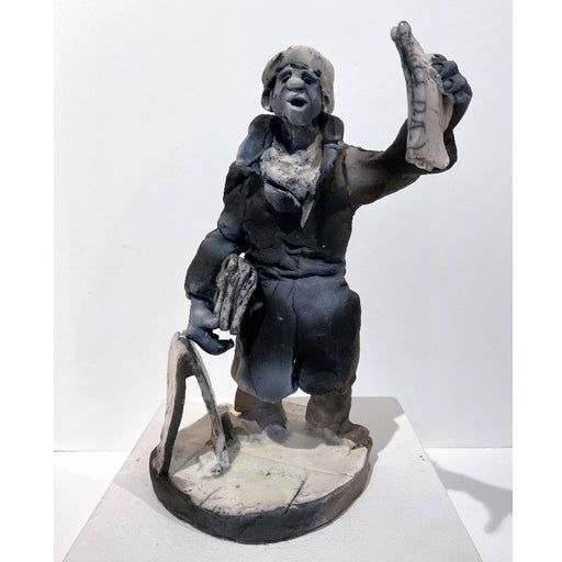 Buy 'Late Night Final', a ceramic sculpture by Yorkshire artist Alistair Brookes. Image shows a grey stylised sculpture of a man wearing a long belter coat gesturing with a ceramic newspaper and pile of them under his arm, he is accompanied by a a frame stand to his left and stood on a round platform. The sculpture sits on a white plinth against a white wall.