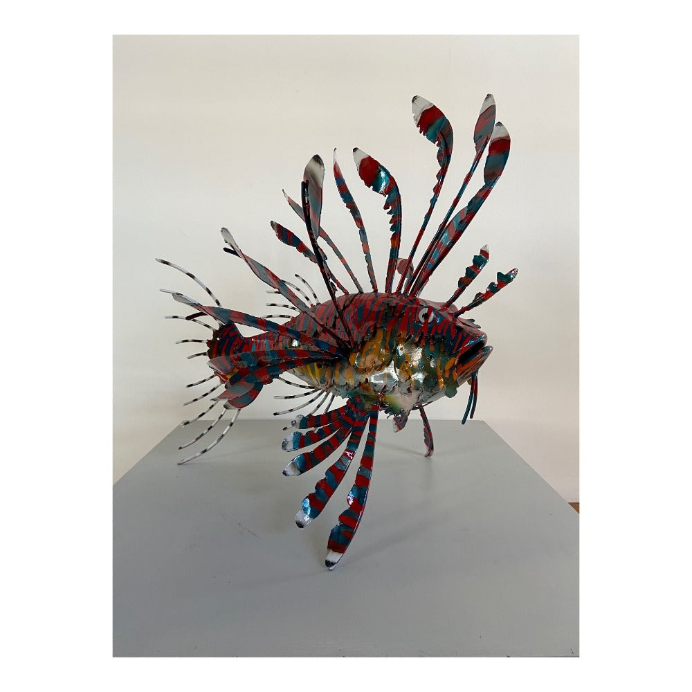 Buy 'Lion Fish' a handmade lacquered steel sculpture by Peter Sales.  Image shows a large sculpture of a lion fish facing to the right and stood on the fins. The fish is predominantly red and teal with orange and white around the gills. The sculpture sits on a white plinth in front of a white wall.