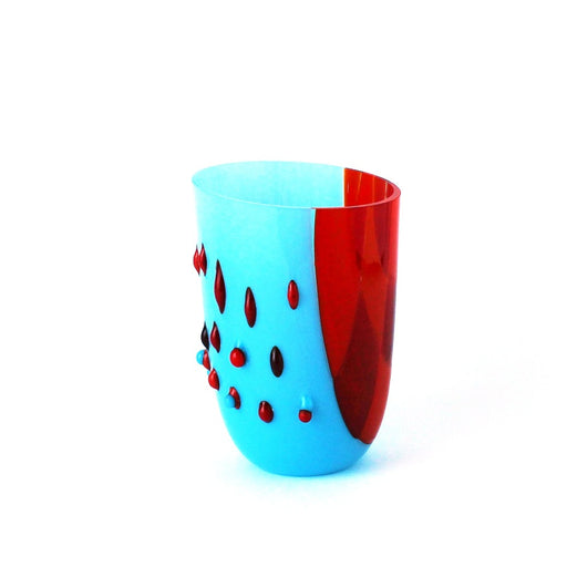 Buy 'Textured Blue and Red Drop-out Vessel', a handmade glass vessel by Catherine Mahe. Image shows a tall vessel-shaped glass sculpture half in light blue decorated with red embellishments and half in red. The sculpture sits on a white background.