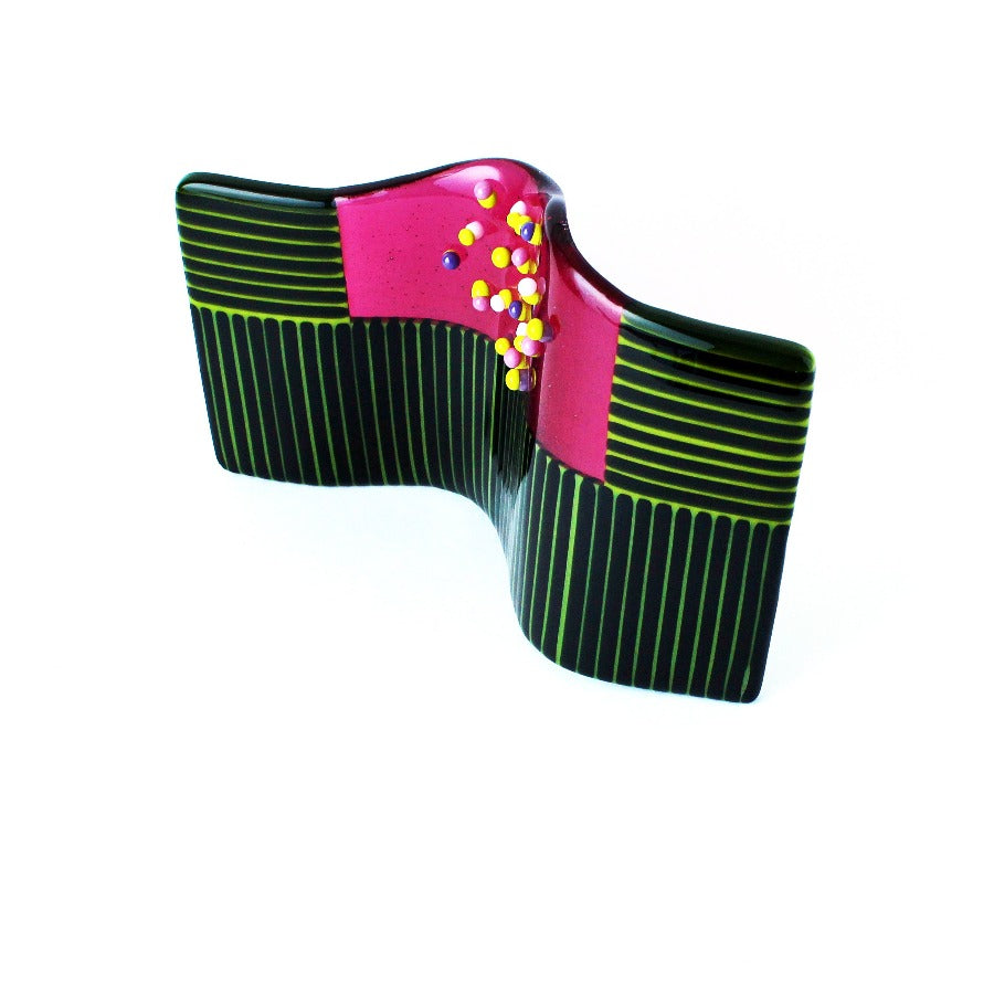 Buy 'Textured Green and Pink Sculpture', a handmade glass sculpture by Catherine Mahe. Image shows a wavy rectangular glass panel sculpture decorated with green and black stripes in the centre of the top half is a pink panel decorated with multi-coloured embellishments.