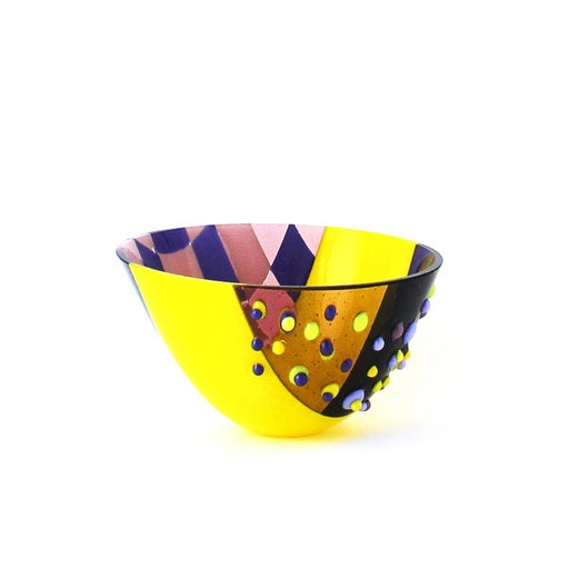 Buy 'Textured Yellow and Purple Drop-out Vessel', a handmade glass vessel by Catherine Mahe. Image shows a bowl-shaped glass sculpture decorated with three panels, one checkerboard design in purple and pink, the middle a vibrant yellow and the third a see-through purple with matching yellow and purple embellishments.
