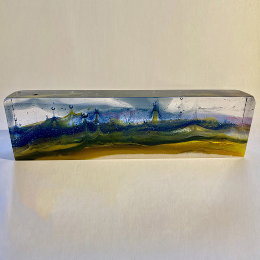 Buy 'In My Dreams' a handmade glass sculpture of a fantasy landscape by Pat Marvell. Image shows a long rectangular block of glass built with clear, blue, green and yellow glass to present an abstract landscape within it. The sculpture sits on a white background.