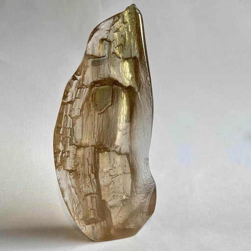 Buy 'Nook' a handmade glass sculpture by Pat Marvell. Image shows a cast glass sculpture with a slight bronze/gold hue in a rough teardrop shape with a bark texture over the surface. The sculpture sits on a grey background.