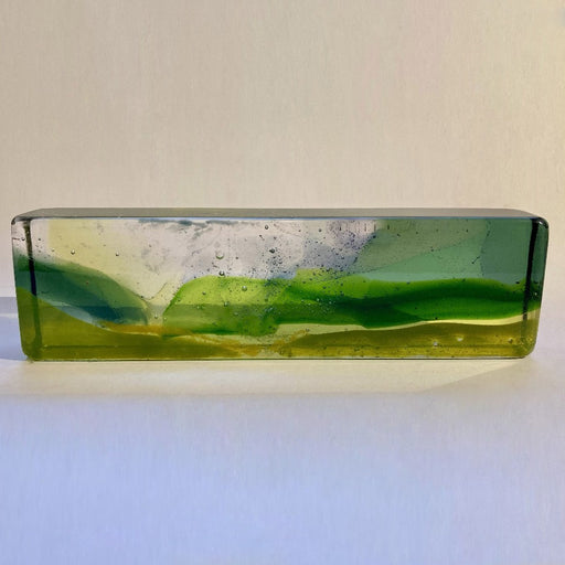 Buy 'Through the Morning Mist' a handmade glass sculpture inspired by the Cornish landscape by Pat Marvell. Image shows a long rectangular glass block built with clear, green and yellow glass to show a vague landscape. The sculpture sits on a white background.