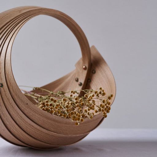Buy handmade original homeware by Jane Crisp at The Biscuit Factory. Image shows a sculptural wooden spiral basket filled with dried flowers sat on white cloth in front of a grey wall.