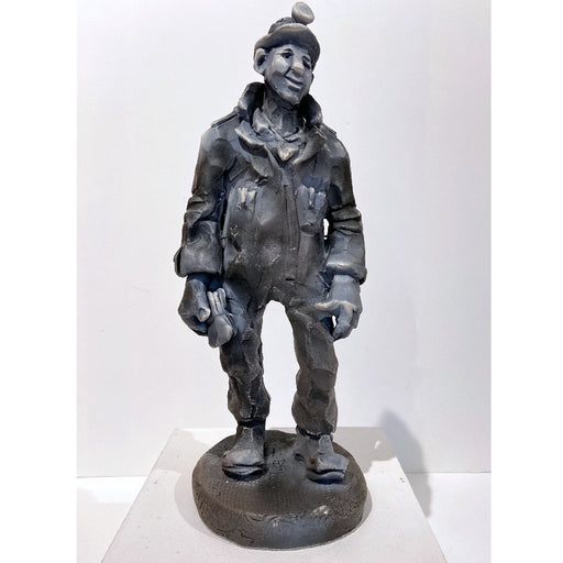 Buy 'Mining Surveyor', a ceramic sculpture of a miner by Yorkshire artist Alistair Brookes. Image shows a grey stylised sculpture of a miner in a boiler suit and a headlamp standing on a small circular slab. The sculpture sits on a white plinth against a white wall.