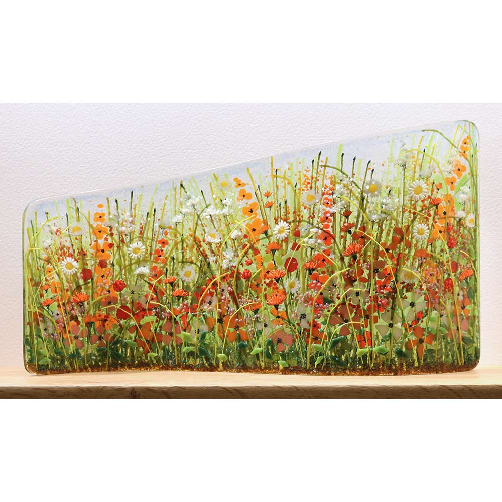 Buy 'Orange Meadow Asymmetric Curve' a handmade glass sculpture by Vandacrafts. Image shows a curved glass panel shorter in height on the left side than the right. The panel is decorated with a floral meadow scene with poppies, daisies and grass - predominately orange and green in colour. The sculpture sits on a wooden shelf on a white background.