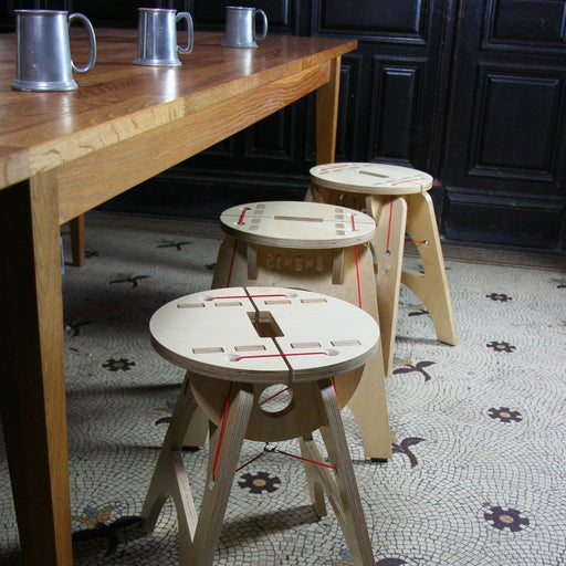 'Stool 8x8x15', a wooden quirky seat by PLYable Design. Image shows a row of light wooden stools made up of flat panels with cut out details and red cord attaching the tops to the legs. They sit on a mosaic tile floor in front of a polish wooden table with grey pewter beer mugs sat on top. In the background is a navy panelled wall.