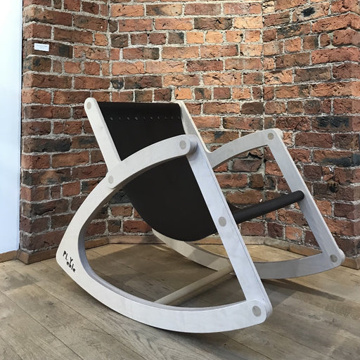 'Wishbone Rocking Chair', a quirky wooden chair by PLYable Design. Image shows a pale wooden rocking chair made up of flat panels of wood, the seat is a piece of dark material which hangs between the two sides. The chair sits on a wooden floor with an exposed brick wall behind it.