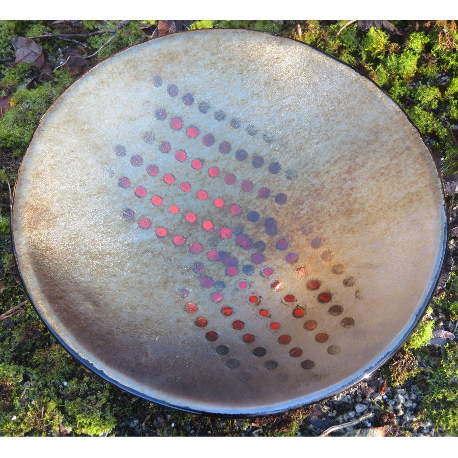 'Shades of 2020 I', a handmade coloured glass dish by Penny Riley-Smith. Image shows a metallic grey circular shallow bowl decorated with dotted patterns in pink, purple and red gradients. The bowl sits on a bed of moss.