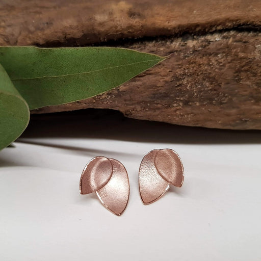 View and buy ethical handmade jewellery online at The Biscuit Factory. 'Rose Fritillaria Petal Earrings' rose gold finished floral studs by Donna Barry. Image shows a pair of copper coloured studs made up of an inverted teardrop overlapped with a smaller inverted teardrop sat on a white surface. In the background is a piece of wood and green leaves.