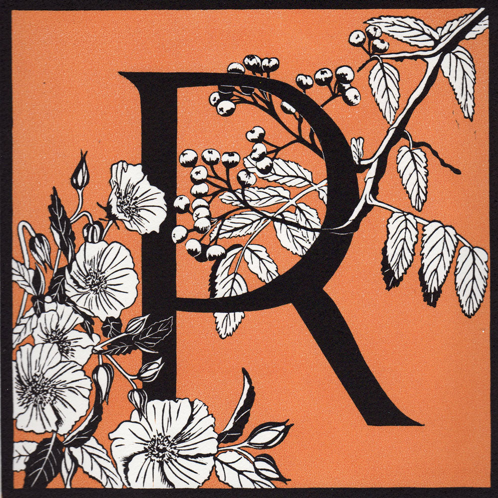 View and buy typography prints by Julie North at The Biscuit Factory. Image shows an orange square with a black border featuring a letter R in the centre decorated by white flowers, leaves and berries.