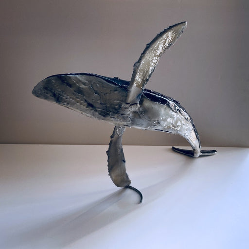 View and buy original sculpture online at The Biscuit Factory. 'Whale I' a handmade lacquered steel sculpture by Peter Sales. Image shows a glossy steel sculpture of a blue whale posed as if leaping from the water with fins spread wide. The sculpture sits on its tail and fin against a white background.