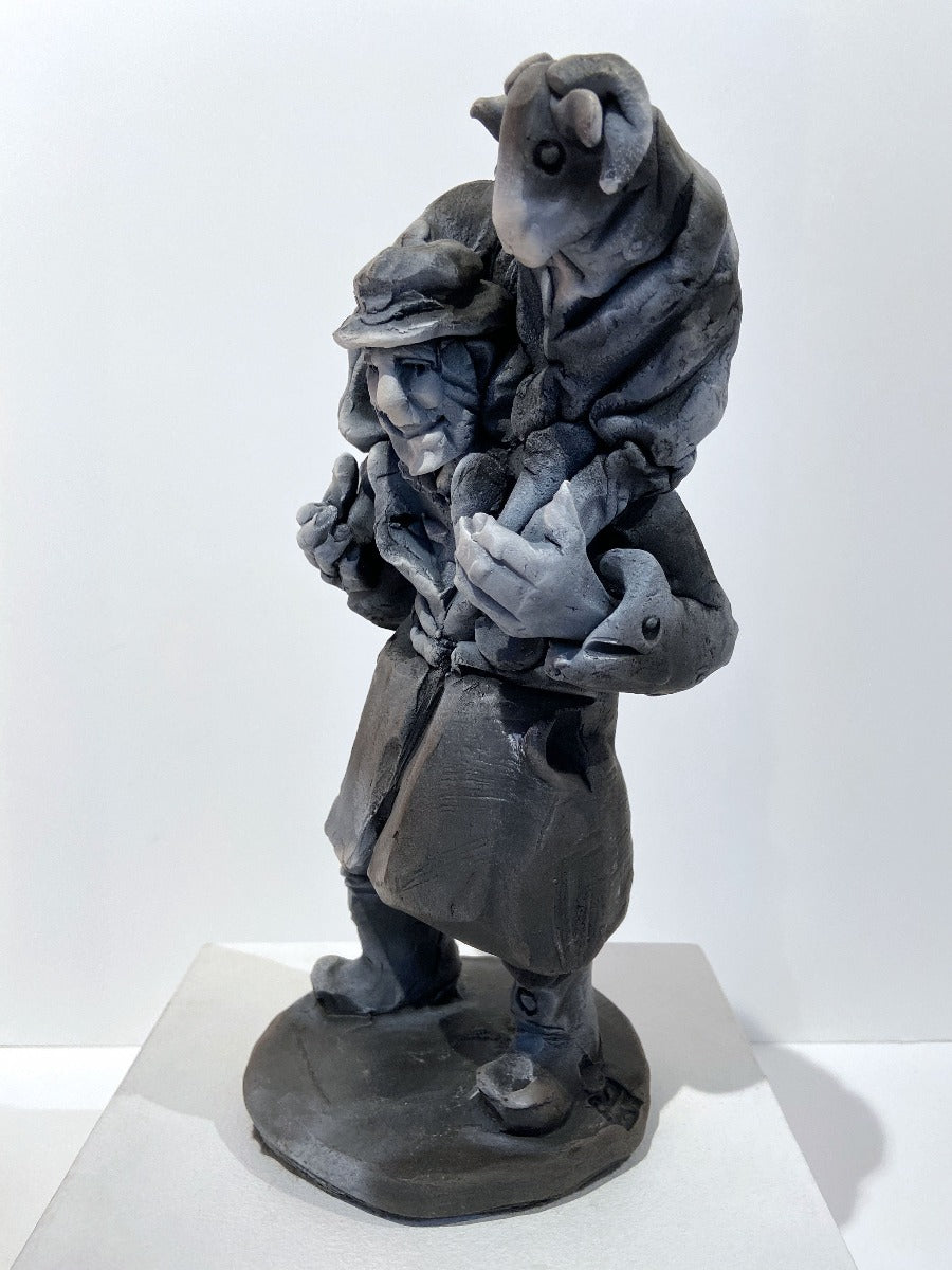 Buy 'Shepherd Carrying Sheep', a ceramic sculpture of an agricultural figure by Yorkshire artist Alistair Brookes. Image shows a stylised grey sculpture of a man with a beard, long belted coat and boots carrying a sheep with curled horns on a circular base. The sculpture sits on a white plinth against a white wall.