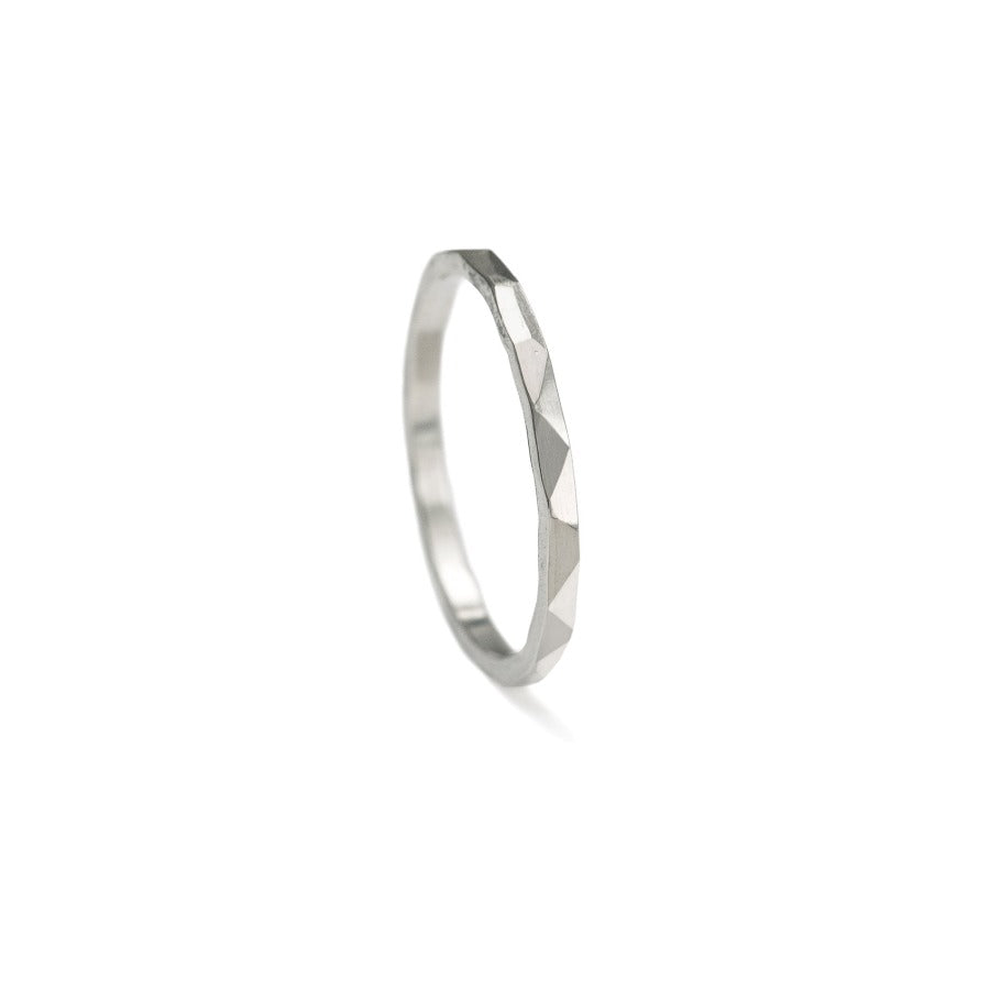 Buy 'Multi-Faceted Ring' handcrafted jewellery by Sarah Ruth Stanford. Image shows a ring sat on its edge on a white background. The surface of the ring is edged and bevelled.