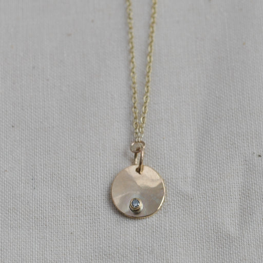 Buy 'Gold Droplet Diamond Necklace' a recycled gold necklace by Sarah Ruth Stanford. Image shows a necklace sat on a beige material background. The necklace is made up of a gold chain with a circular gold pendant subtly bevelled with a diamond set on the bottom edge.