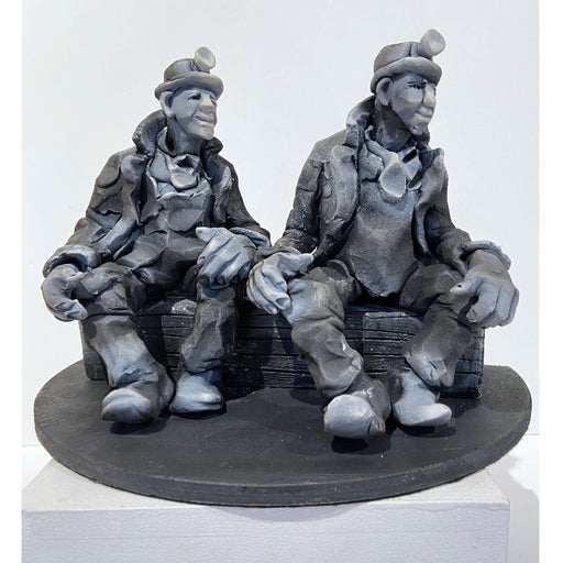 Buy 'Summints Up', a ceramic sculpture of miners by Yorkshire artist Alistair Brookes. Image shows a stylised grey sculpture of two miners wearing headlamps, large coast and boots sat on a long log both looking to the right. The sculpture is sat on a white plinth against a white wall.