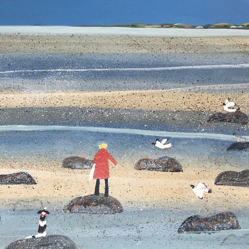 'Low Tide Alnmouth', a landscape painting by Barbara Pierson. Image shows a landscape painting of a beach scene with large rocks scattered in the foreground and 3 black and white birds in varying stages of flight to the right. A person in a red coat and a white and brown spotted dog stand on a different rock with their back to the viewer.