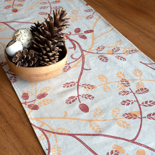 Printed textile table runner by Astrid Weigel. Image shows a linen coloured table runner printed with red and yellow leaves, sat upon a polished wooden table and accompanied by a wooden bowl of acorns.