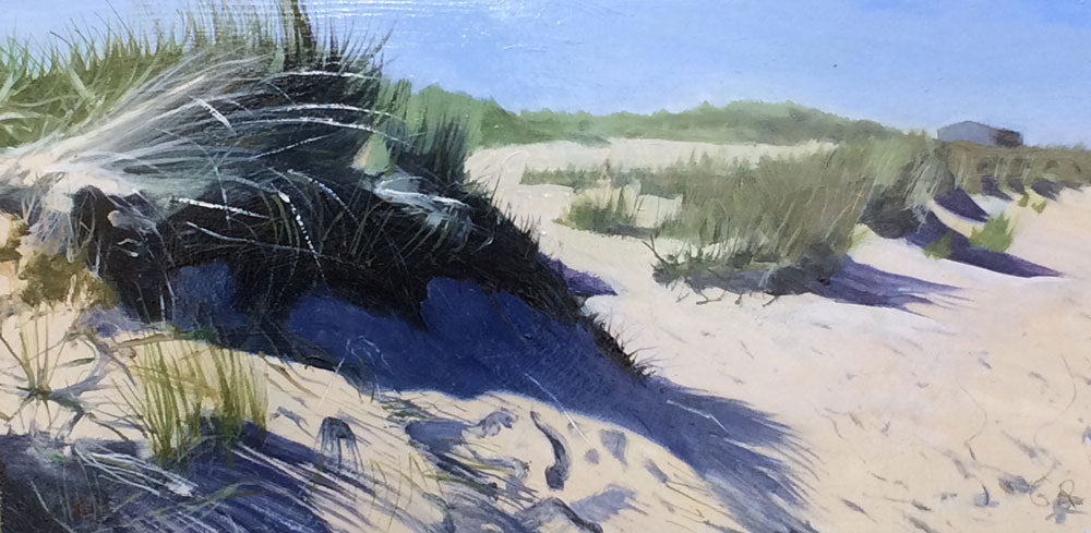 Buy original coastal landscape paintings by Graham Rider at The Biscuit Factory. Image shows oil painting of sand dunes on a back drop of blue sky with a grey building in the distance