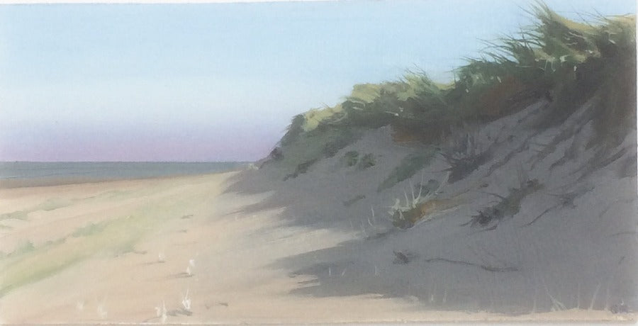 Buy 'Towards Warkworth', a coastal landscape by Graham Rider. Image shows a beach scene with grass covered sand dunes to the right and a flat expanse of sand to the left. In the distance is a calm sea and a pink hue in the sky.