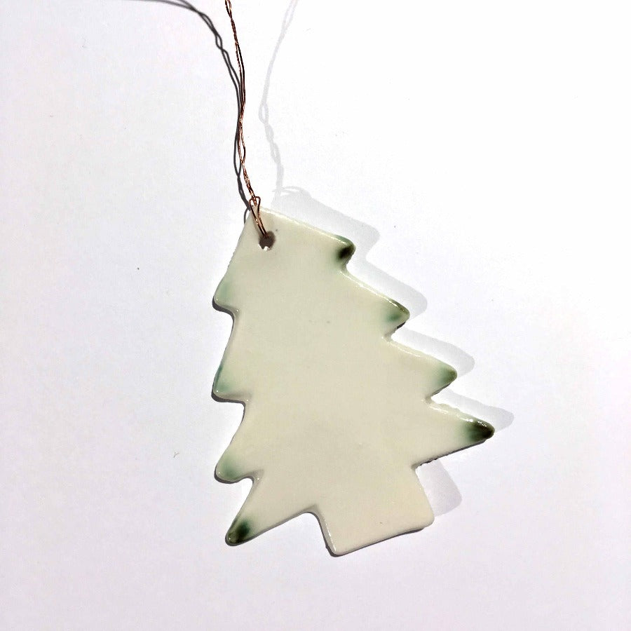 Buy 'Tree Christmas Decoration', a ceramic tree ornament by Kirsty Adams. Image shows a cream ceramic tree silhouette tipped with a bottle green glaze, lay flat on a white surface.